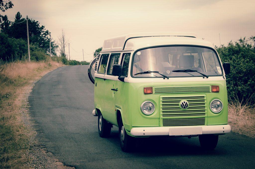 Grüner alter VW-Bulli auf einer Straße unterwegs