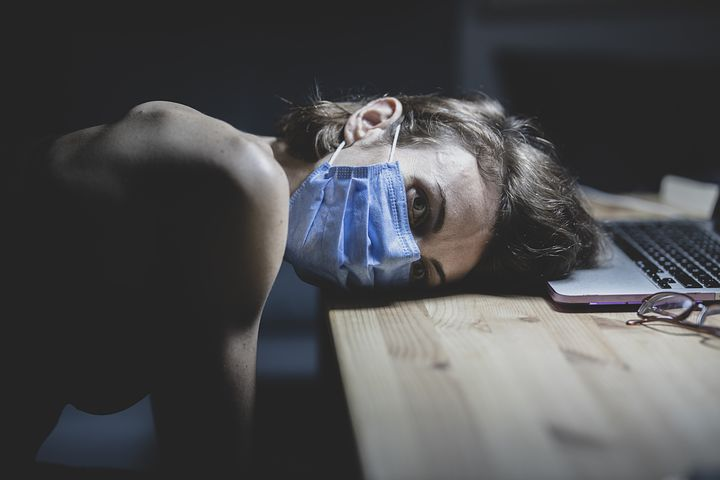 Frau mit Maske, die mit dem Kopf auf dem Tisch liegt