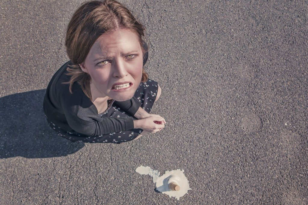 Frau ist ärgerlich, weil ihr Eis auf den Boden gefallen ist.