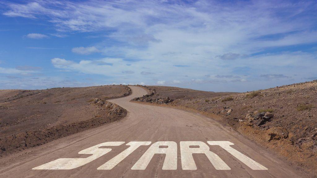 """Eine Straße auf einen Hügel hinaus, am Anfang steht """"Start"""" auf dem Boden"""