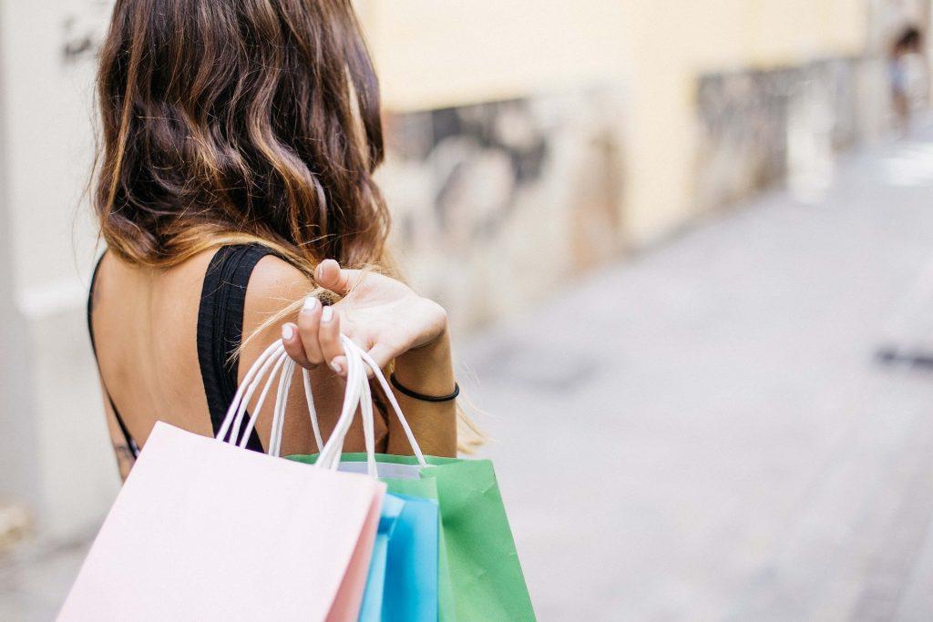 Von hinten zu sehende Frau mit Shoppingtüten über der Schulter