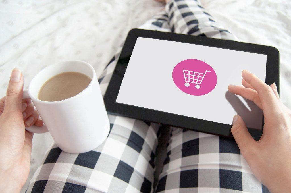 Frau mit Kaffee und Tablet, auf dem ein Warenkorb zu sehen ist