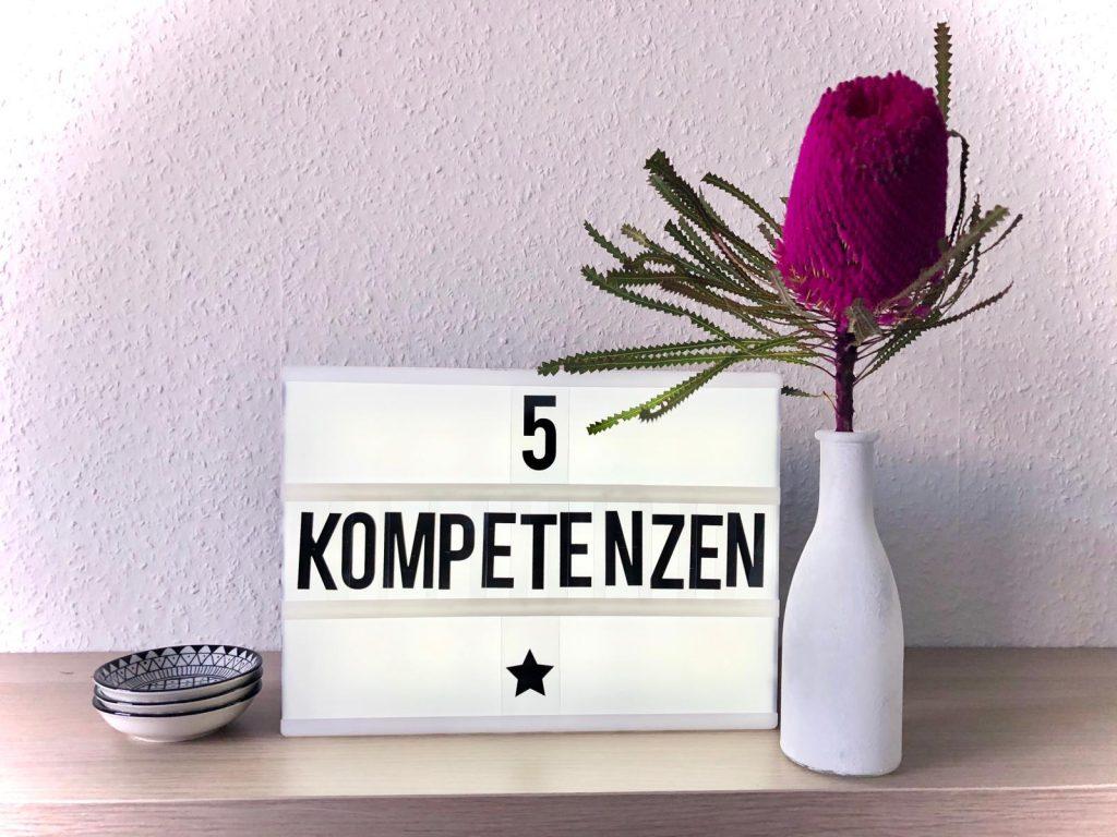 Auf einem Lichtboard steht 5 Kompetenzen, daneben eine Blume