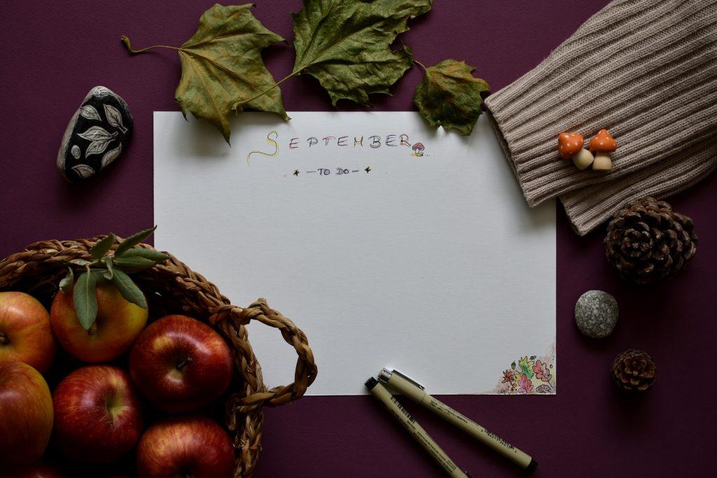 eine to-do Liste für den September . Neben der Liste ist ein Korb mit Äpfeln und anderer Herbstdekoration