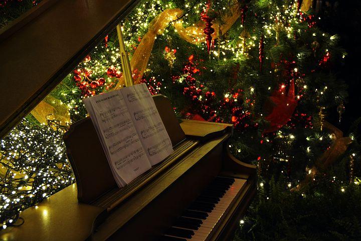 Klavier mit Notenheft, im Hintergrund ein beleuchteter Weihnachtsbaum