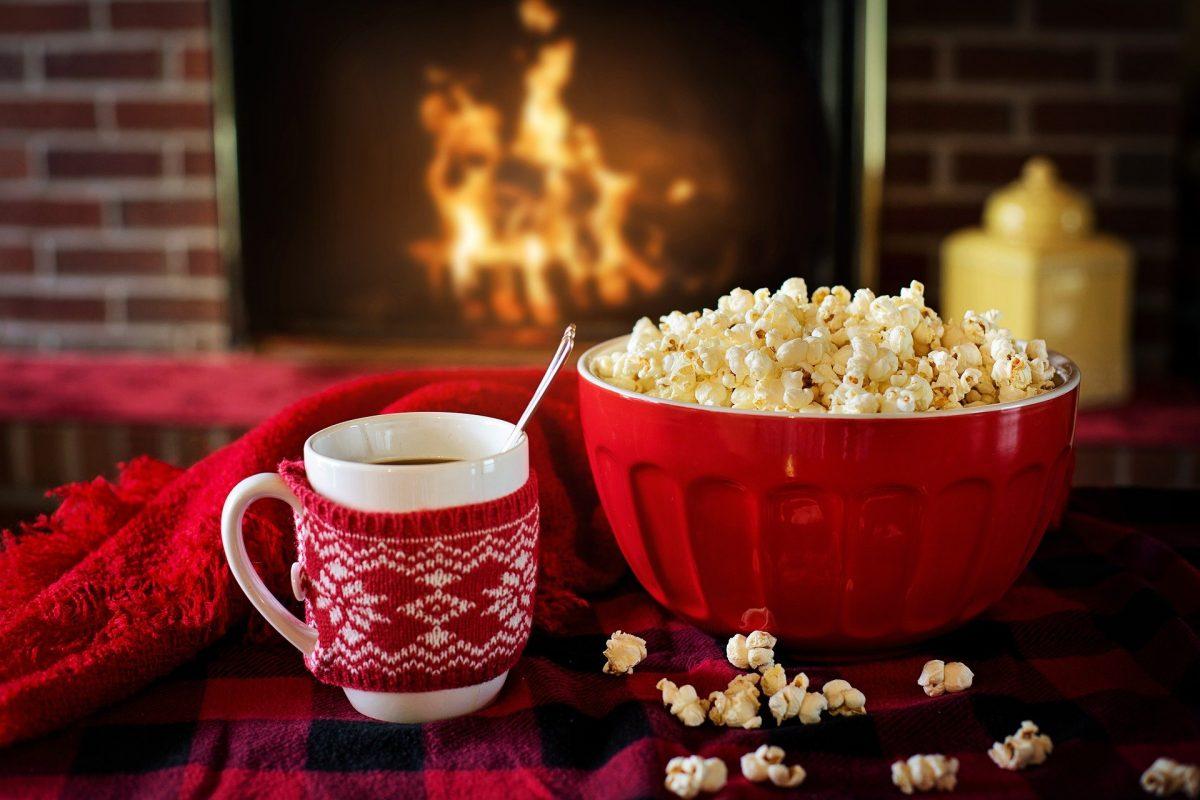 Umhäkelte Tasse und Popcornschale vor einem flackernden Kamin