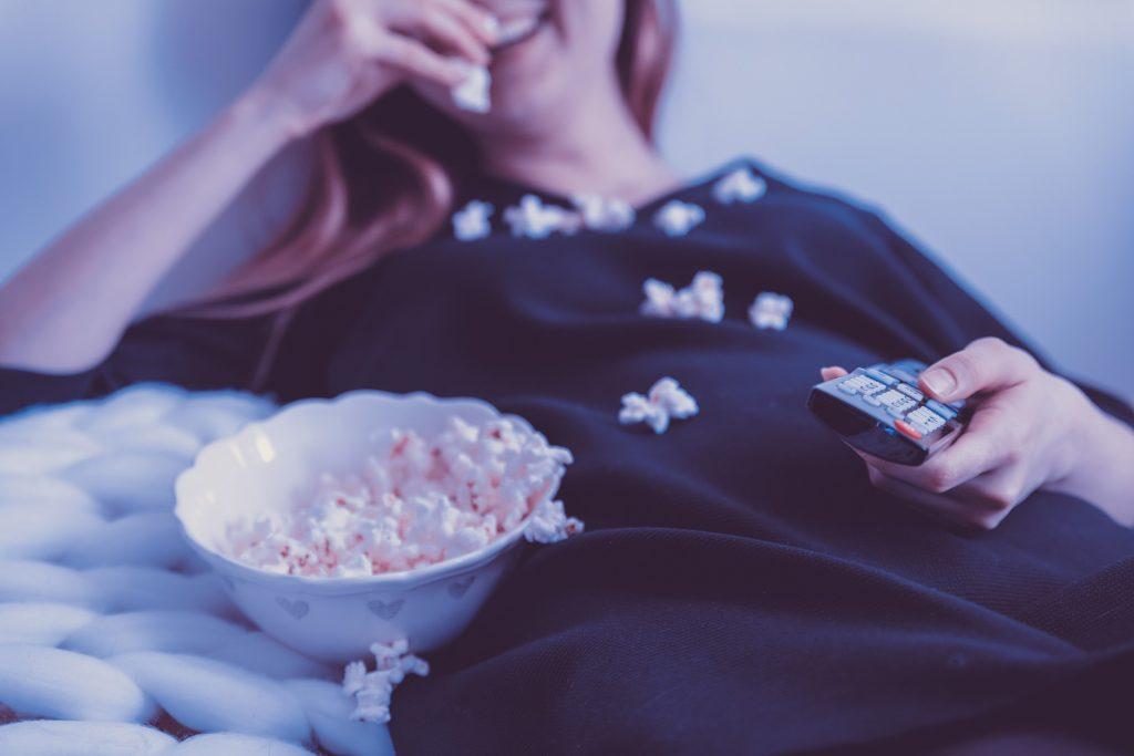 Eine Frau liegt gemütlich auf einer Couch mit Fernbedienung in der Hand und isst Popcorn