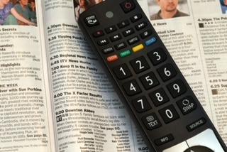 Fernbedienung auf einer aufgeschlagenen Programmzeitschrift; es läuft Downton Abbey