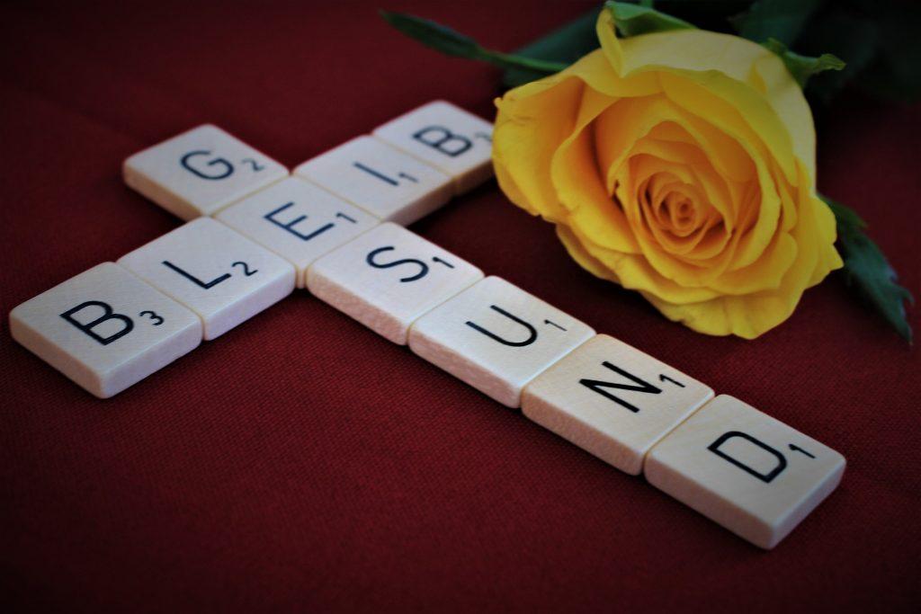 """Aus Scrabble-Steinen gelegte Wort """"Bleib gesund"""" in Kreuzform"""