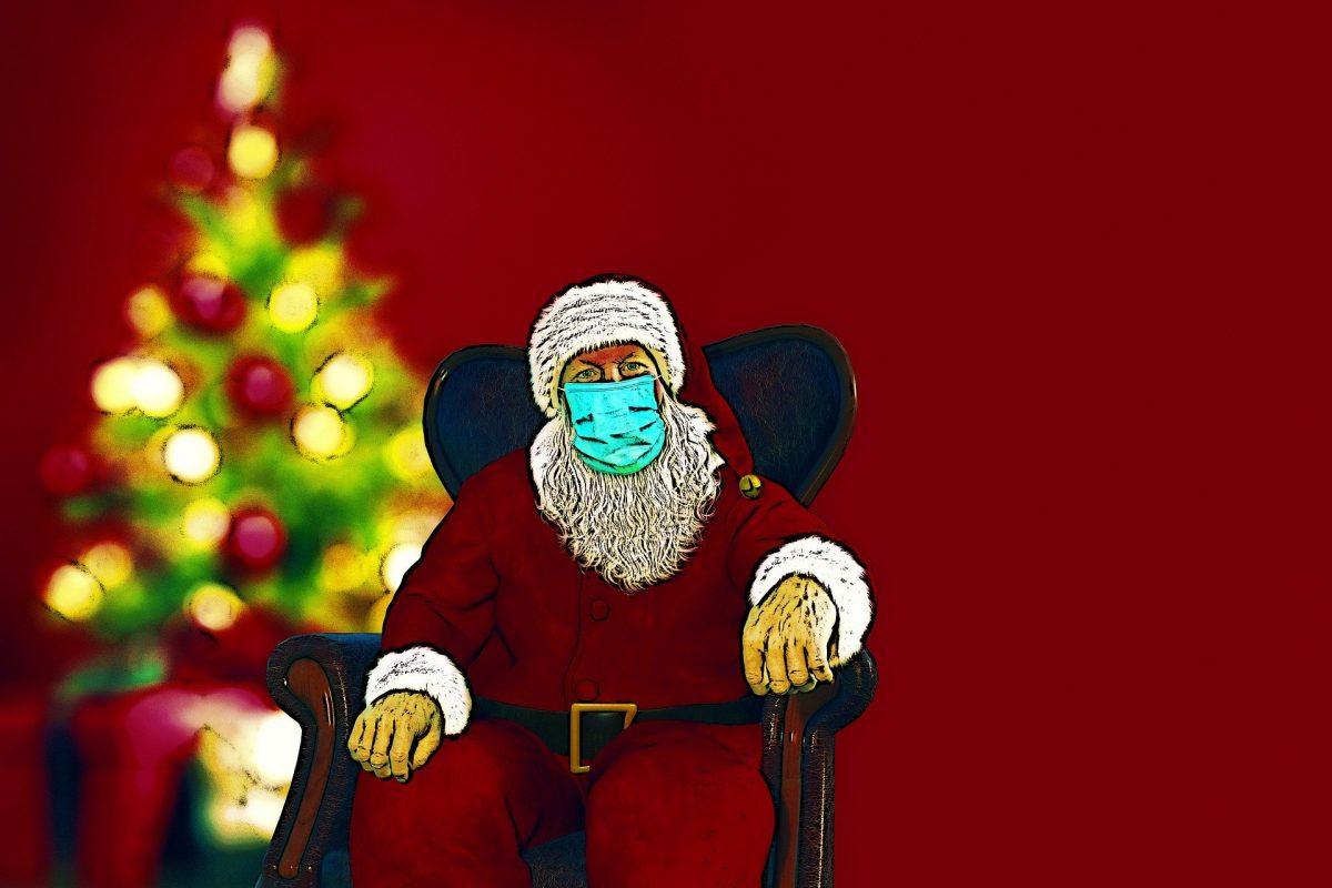 Weihnachtsmann mit Maske vor Tannenbaum