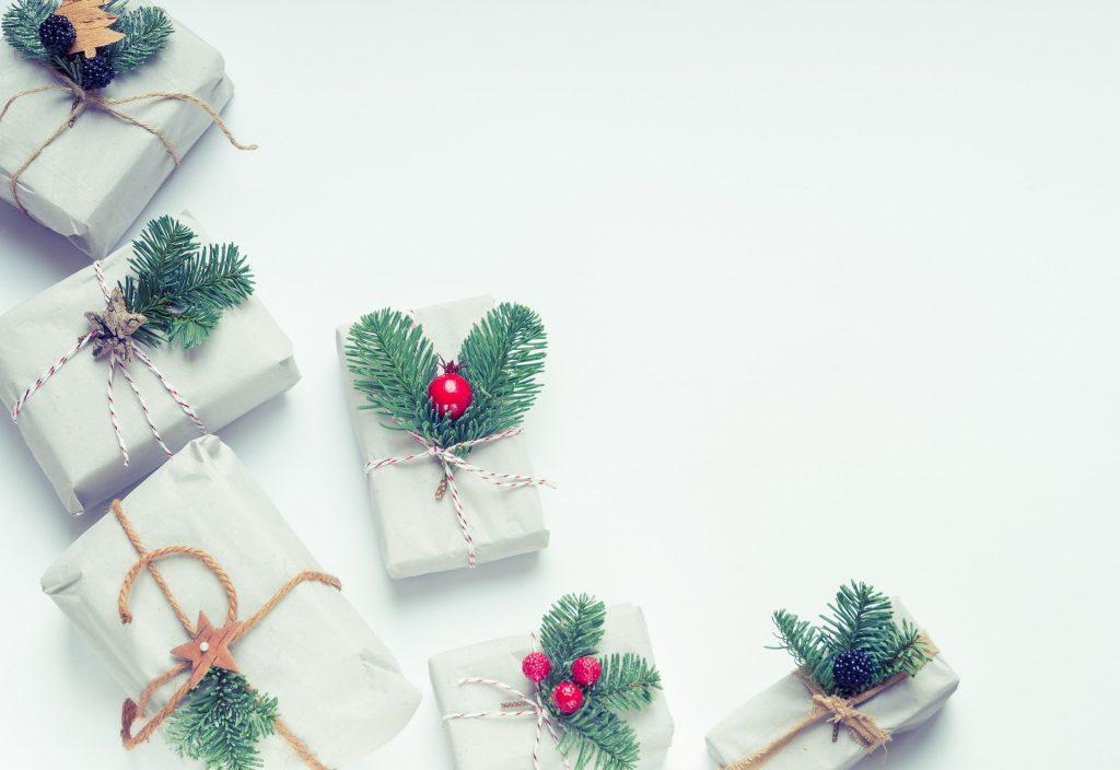 Sechs kleine Geschenke in weißem Papier verpackt. Als Deko wurden kleine Tannenzweige in die Kordeln gesteckt.