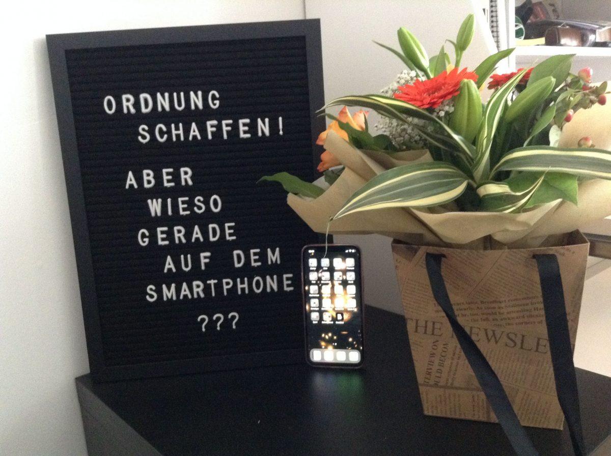"""Letterboard mit dem Text """"Ordnung schaffen - auf dem Smartphone?"""", Smartphone mit leuchtendem Bildschirm, Blumenstrauß"""