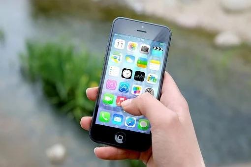 Smartphone mit verschiedenen Apps auf dem Startbildschirm in der Hand einer Frau