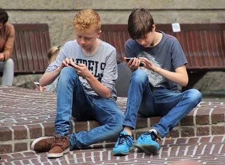 Zwei Jungs, die auf ihren Smartphones spielen