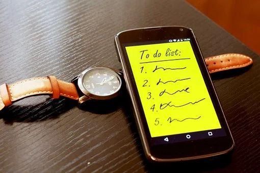 ToDo-Liste auf einem Smartphone und eine Armbanduhr auf einem Tisch