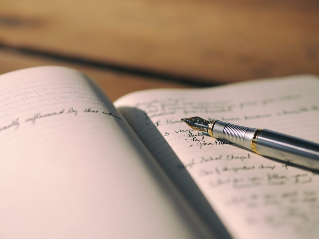 offenes Notizbuch mit handgeschriebenem Text drin, darauf ein Füllfederhalter