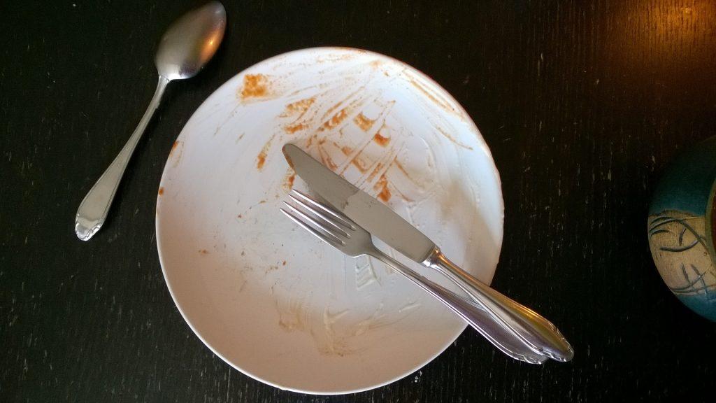 Ein verdreckter Teller mit Besteck.