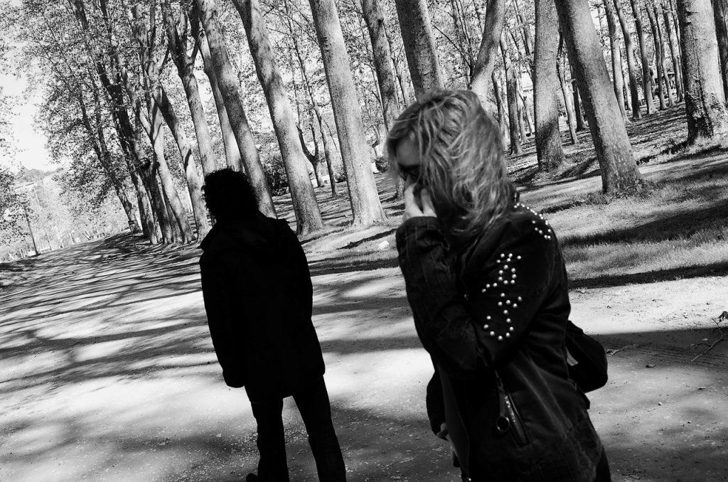 Schwarz-weiß-Bild, Waldweg, im Vordergrund steht eine Frau, jemand anderes geht weg