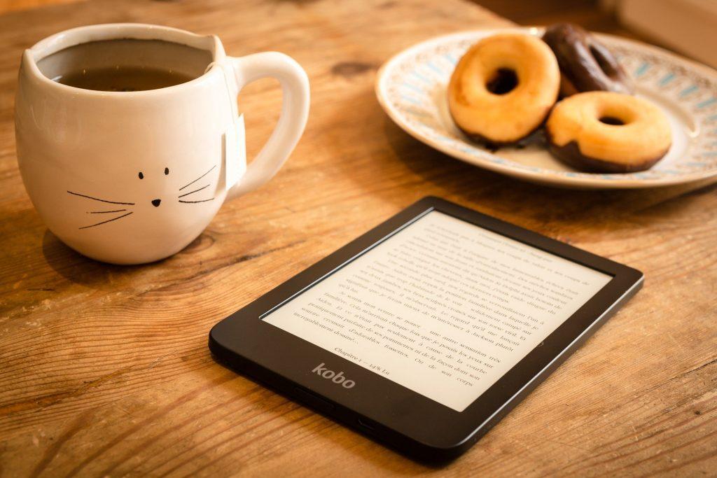 E-Reader auf Holztisch, Donuts und Teetasse