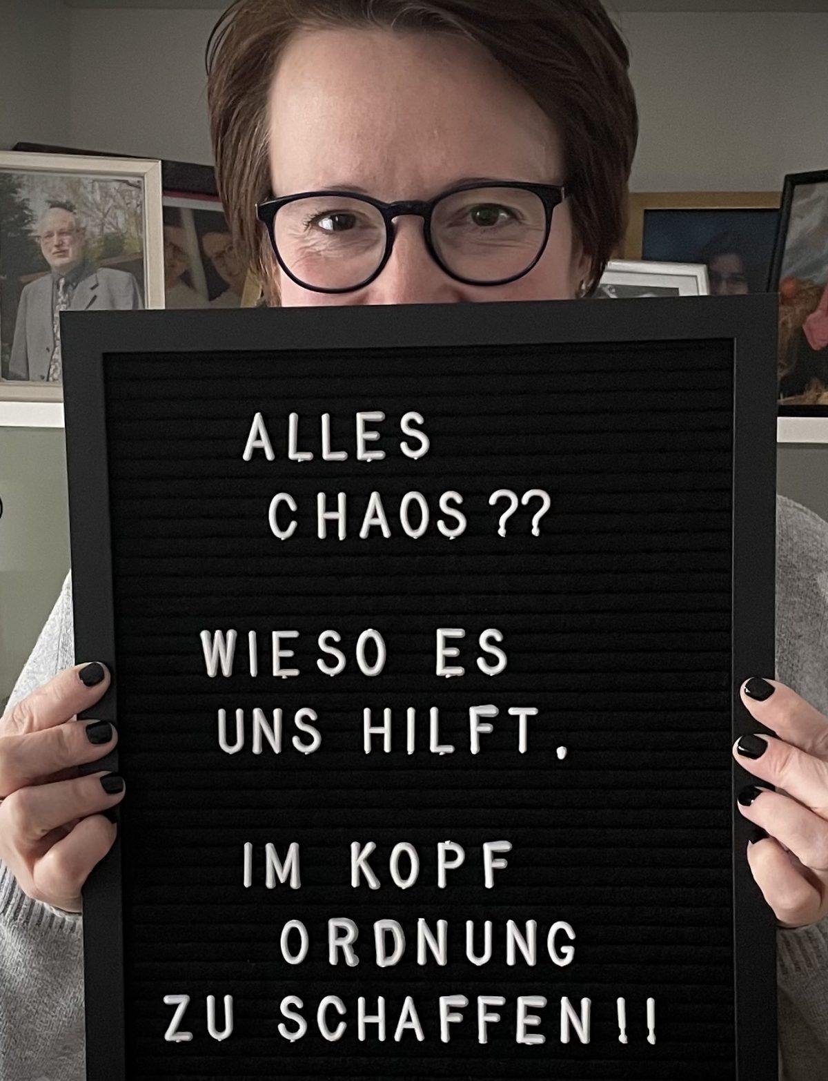 Bernadette mit Schild in den Händen mit Text: Alles Chaos? Wieso es uns hilft, im Kopf aufzuräumen!