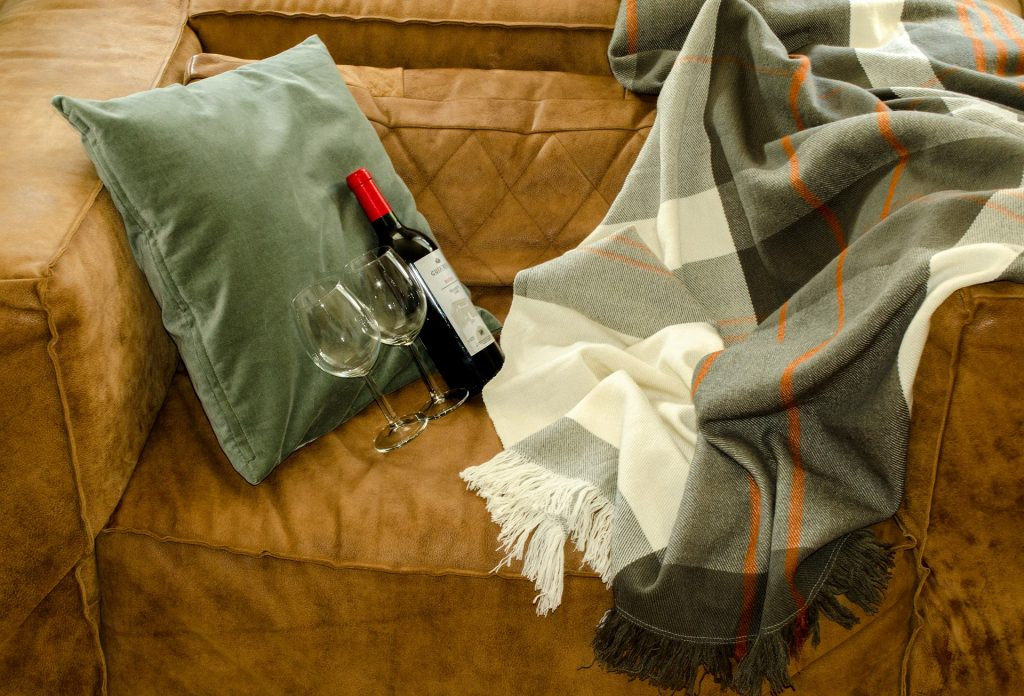 ein braunes Sofa. auf dem liegt ein grünes Kissen und eine grüne Decke. Vor dem Kissen würden zwei Weingläser und eine Flasche Wein arrangiert.