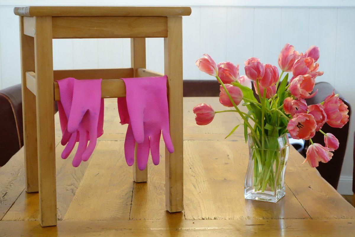 pinke Gummihandschuhe über Stuhl, daneben Tulpenstrauß in Blumenvase