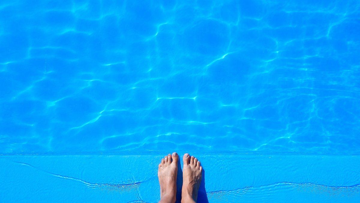 nackte Füße am Beckenrand vom Schwimmbad