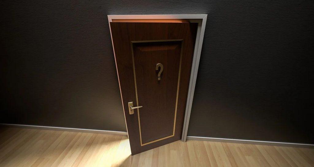 Einen Spalt breit geöffnete Tür mit Fragezeichen darauf, durch die etwas Licht fällt