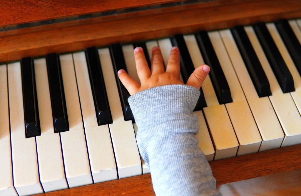 Eine Klaviertastatur mit einer Kinderhand