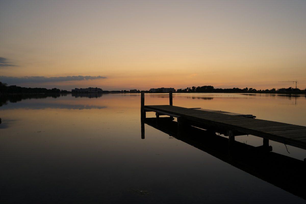 Abenddämmerung, langer Steg, der ins Wasser reicht