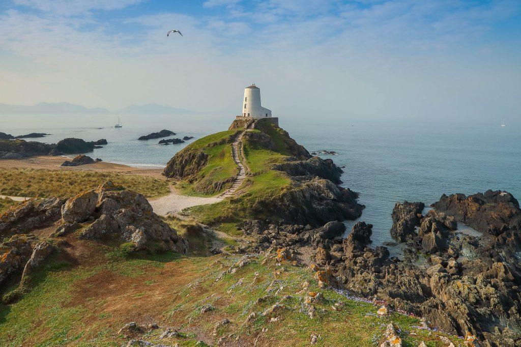weißer Leuchtturm, Meer im Hintergrund, Weg mit Stufen, die zum Leuchtturm hinführen.