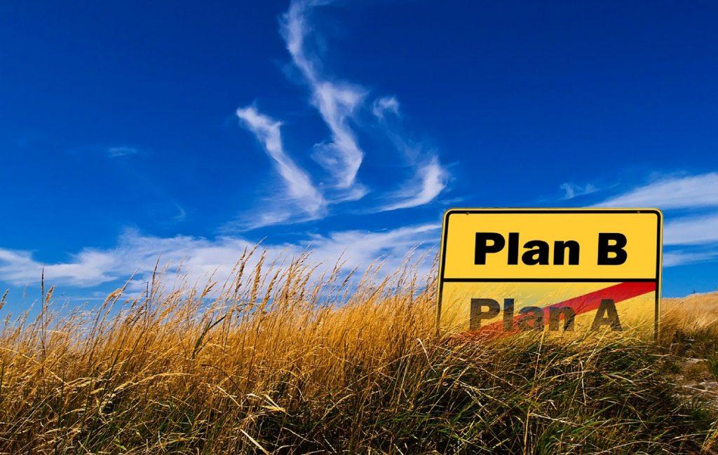 Blauer Himmel, Wiese mit Ortseingangsschild: Plan A durchgestrichen, Plan B