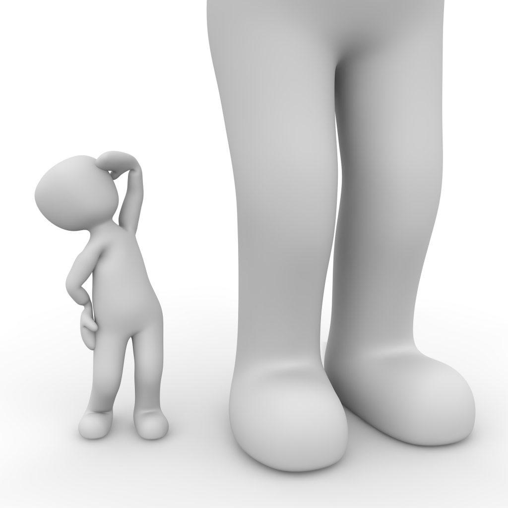 zwei weiße Figuren, kleine Figur schaut zu großer Figur hoch, von der nur die Füße zu sehen sind. Unerreichbar