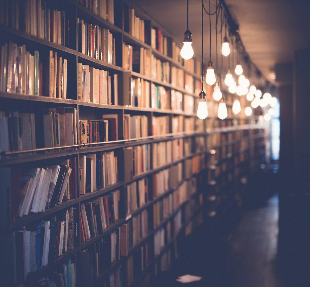 langes Buchregal, von der Decke hängen Glühbirnen an Bändern
