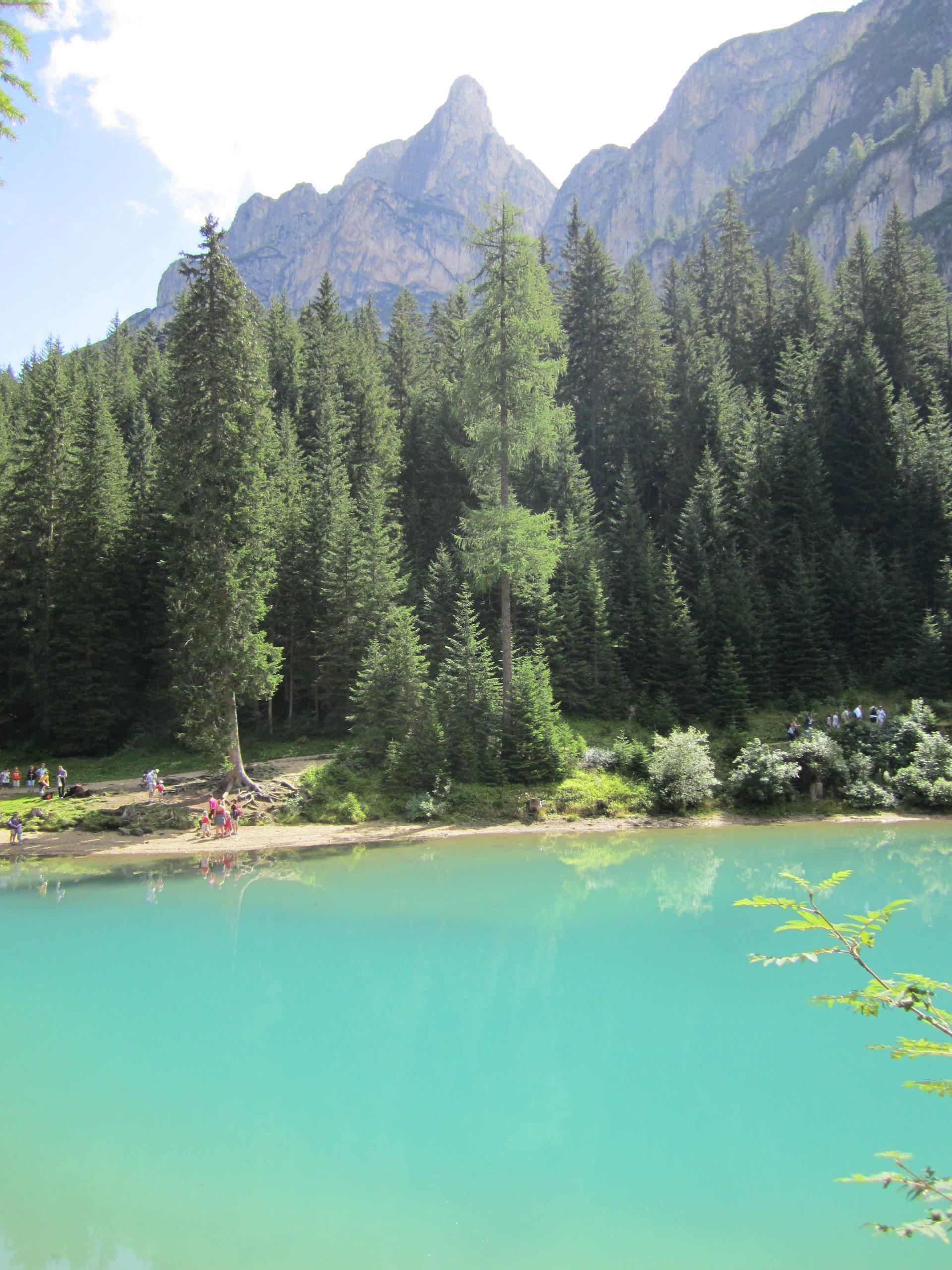 Bergsee mit Bäumen und Menschen am anderen Ufer