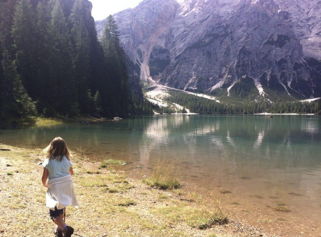 Mädchen mit Wanderstock läuft am Ufer eines sonnenbeschienenen Bergsees entlang