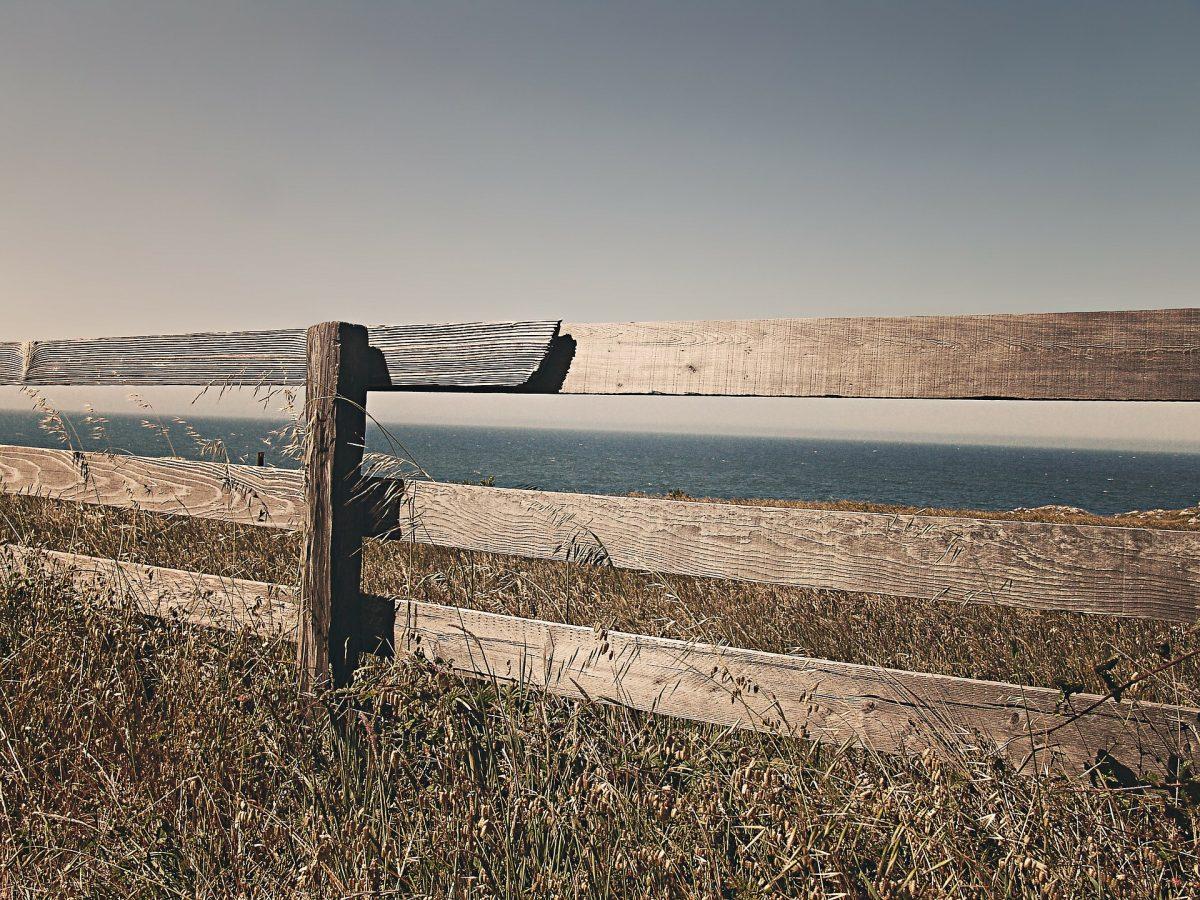 Zaun auf einer Wiese, im Hintergrund das Meer