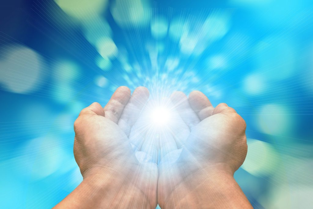 Zusammengelegte Hände. Hinter diesen leuchtet die Sonne