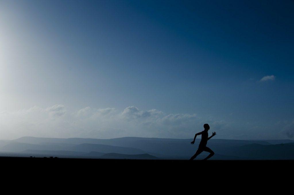 Ein Läufer. Im Hintergrund Berge.
